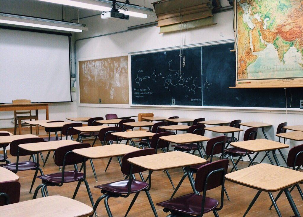 Vacinação e a volta às aulas, na foto uma sala de aula vazia com cadeiras de madeira, um quadro negro a direita e um mapa mundi também a direita.